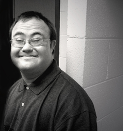black and white portrait of a man with down syndrome smiling. Photo credit: Jenny Erickson
