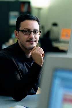 photo of young hispanic man sitting at desk