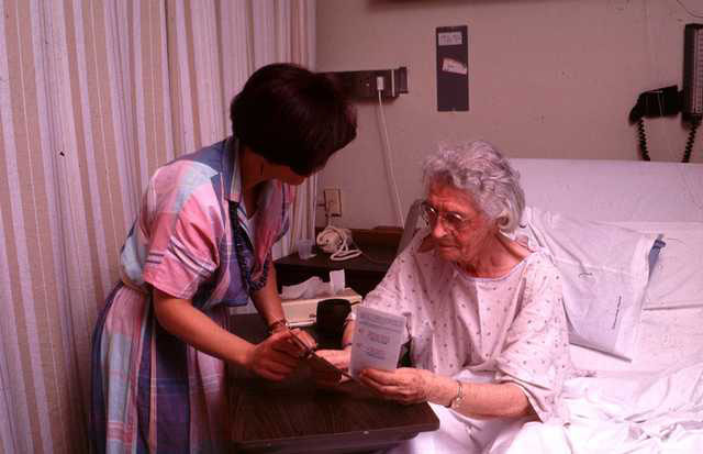 nurse reviews paperwork with older woman