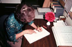 photo of woman at a table writing